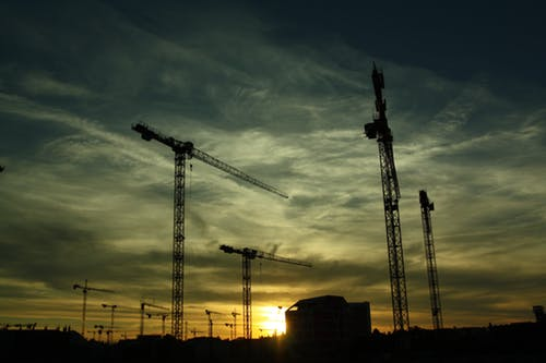 four cranes on a construction site